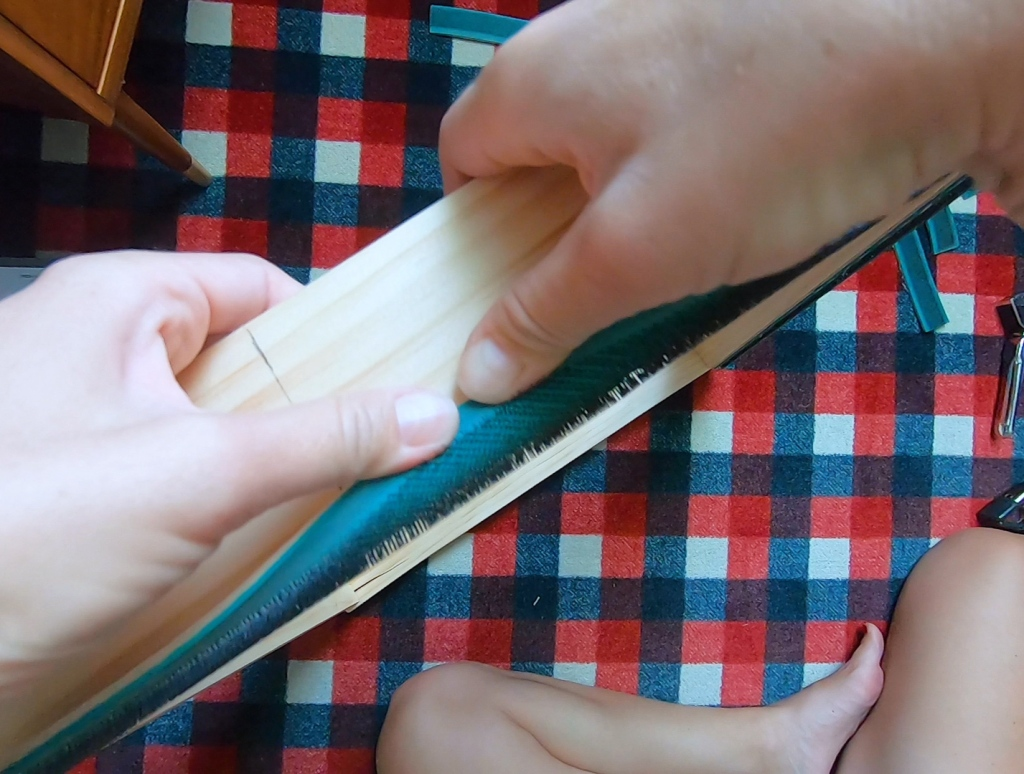 Bend the gripper strip over the side and staple